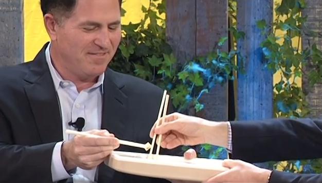 Michael Dell isst eine Laptop-Verpackung aus Pilzen vor laufender Kamera