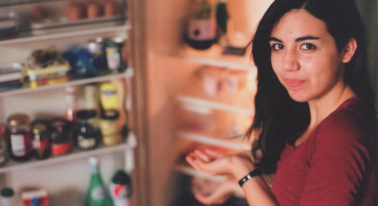 Mädchen vor geöffnetem Kühlschrank