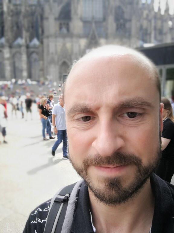 Foto wirkt unecht und das liegt nicht nur daran, dass der Typ auf dem Bild kaum noch Haare hat. Mein Gesicht wirkt seltsam verzogen, die Unschärfe hat hier eher den Anmut eines schlecht hineinkopierten Weichzeichners.