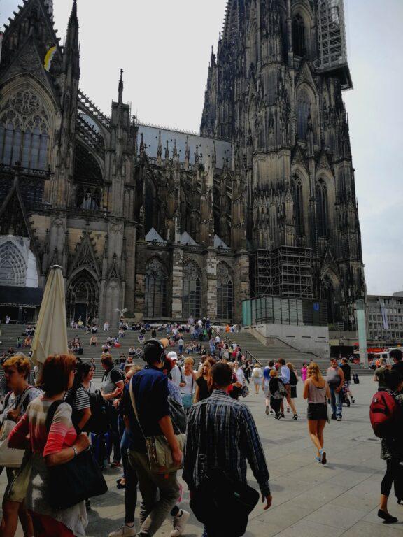 Bild an einem hellen Tag vor dem Kölner Dom aufgenommen. Die Kamera hat die Helligkeit etwas heruntergepegelt. Mir gefallen die leuchtenden Farben im Vordergrund.