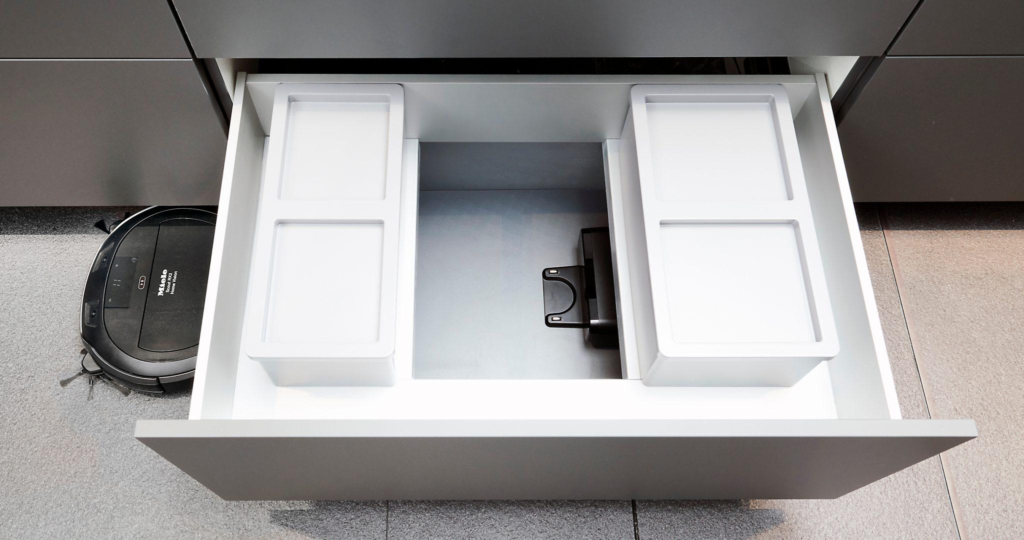 Der Saugroboter Miele RX2 verschwindet im Küchenschrank (Bild: Miele)