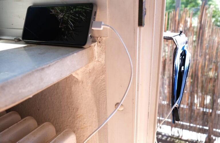 Ideal ist diese Konstruktion nicht, aber notwendig. Das Solarladegerät liegt draußen auf dem Balkon, das Smartphone, das es lädt, bleibt drinnen auf der Fensterbank halbwegs kühl.