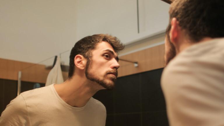 Mann mit Bart vor Spiegel