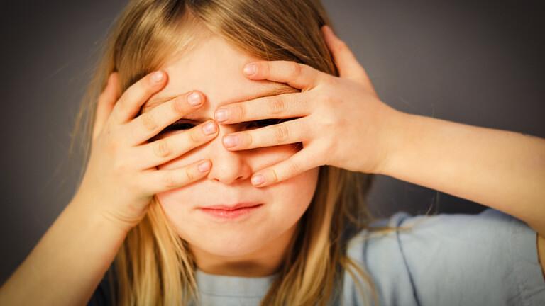 Kind hält Hand vor Augen